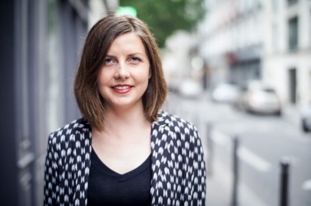 The author of Travel Solo Anyway, Jessica Korteman, standing in a street in Paris with a shoulder length bob, red lips, and a black and white patterned blazer over a plain black top.
