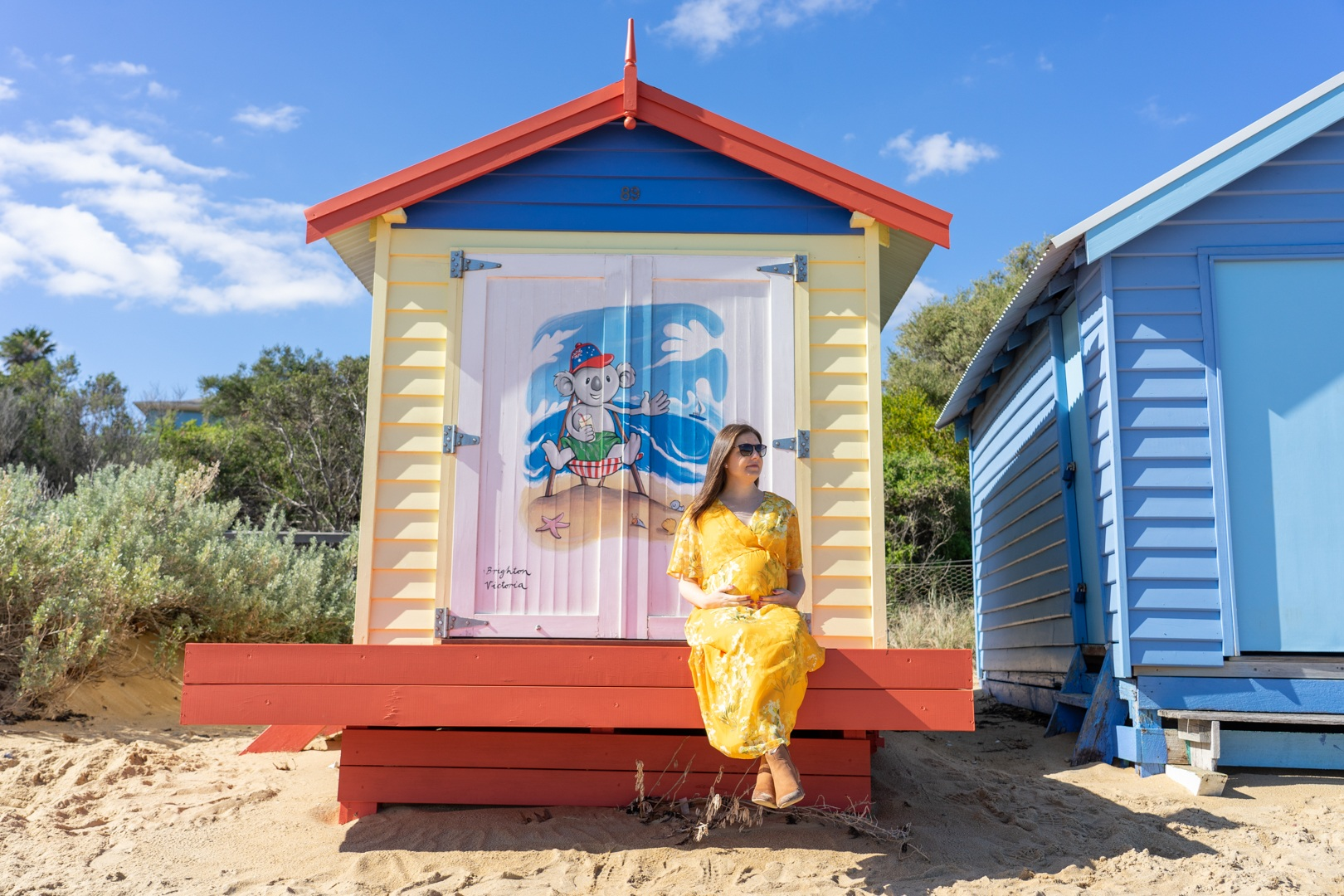 Me (Jess) sitting in front of a Blinky Bill designed Brighton Beach Box in Melbourne, Victoria, holding my pregnant belly.
