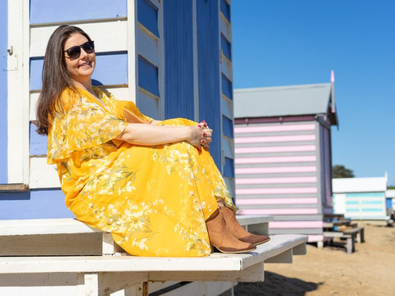 Me (Jess) sitting on the ledge of one of the Brighton Beach Boxes in Melbourne, Victoria, Australia.