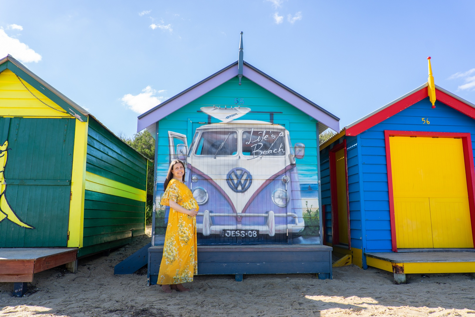Me (Jess) standing in front of one of the Brighton Beach Boxes in Melbourne, Victoria, Australia, holding my pregnant belly. The mural on the box says 'Life's a Beach' over the image of a campervan and has the name 'Jess' on the number plate.