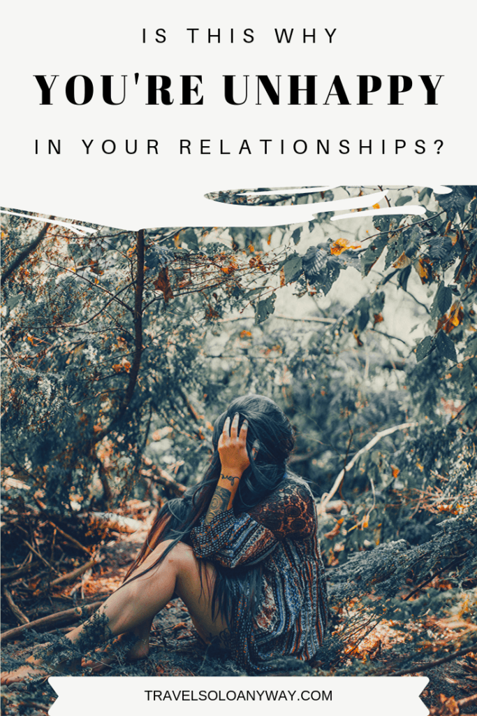 Pin for this post, which says 'Is this why you're unhappy in your relationships?' at the top, has a woman sitting on a forest floor with a hand over her face in the middle, and this website travelsoloanyway.com written at the bottom.