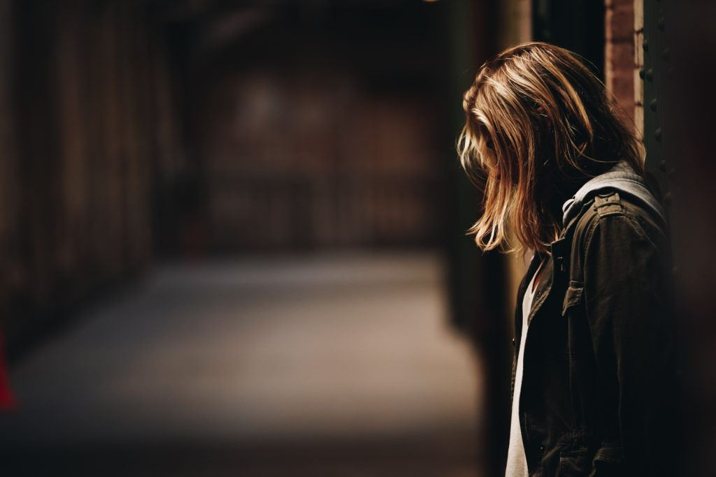 A woman stands head down with her back against a wall in a darkened corridor.