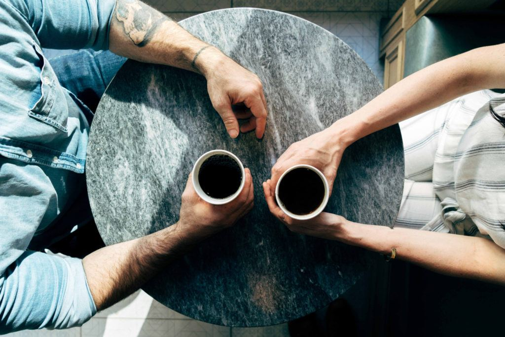 A bird's eye view of a couple sitting across from one another at a small table with their hands around coffee cups.