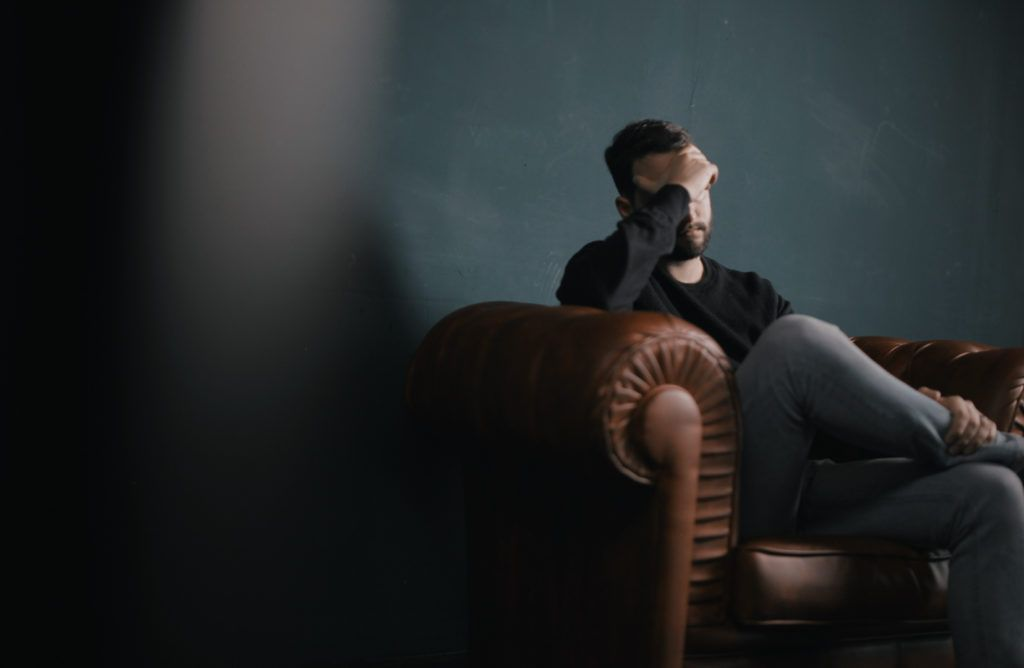 Man sitting alone on a sofa with his hand over his forehead and eyes, seemingly unhappy or upset.