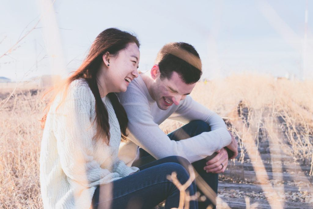 A man and a woman sit side-by-side in a field laughing and enjoying each other's company.