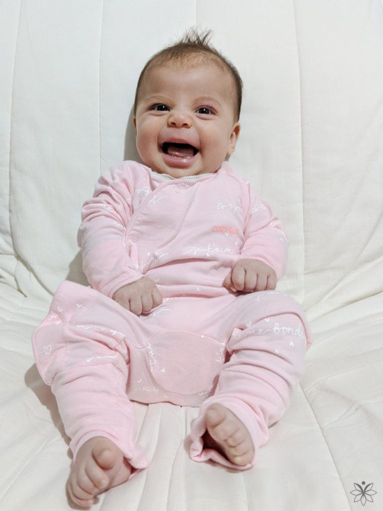 Author's baby sits in a white chair wearing a pink onsie and a big smile.