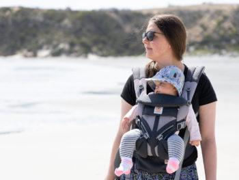 Author stands on a beach looking out to the bay with baby strapped to her chest in baby carrier.
