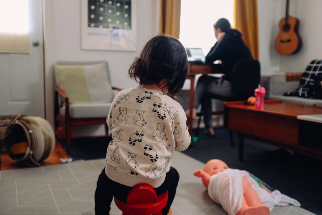 Woman sits at home by a desk in the corner, while a young child sits in the foreground with a doll laying on the floor beside her.