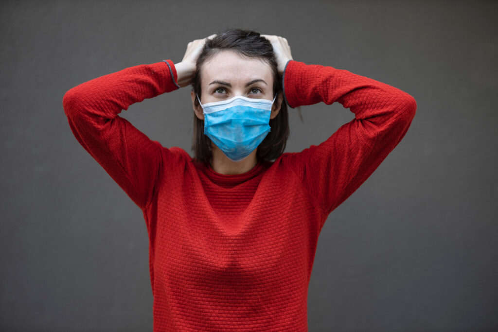 A woman in a red sweater stands with her hands on her head while wearing a face mask.