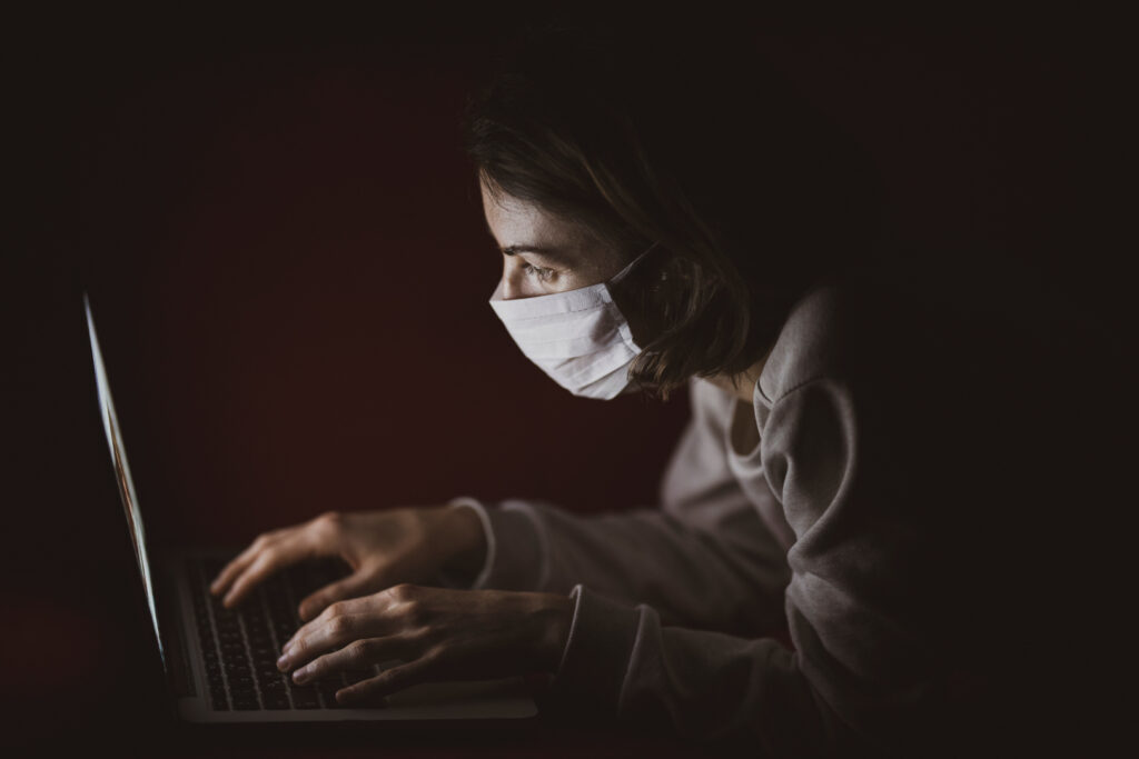 A woman wearing a face mask is lying down in the dark while typing away at the laptop in front of her.