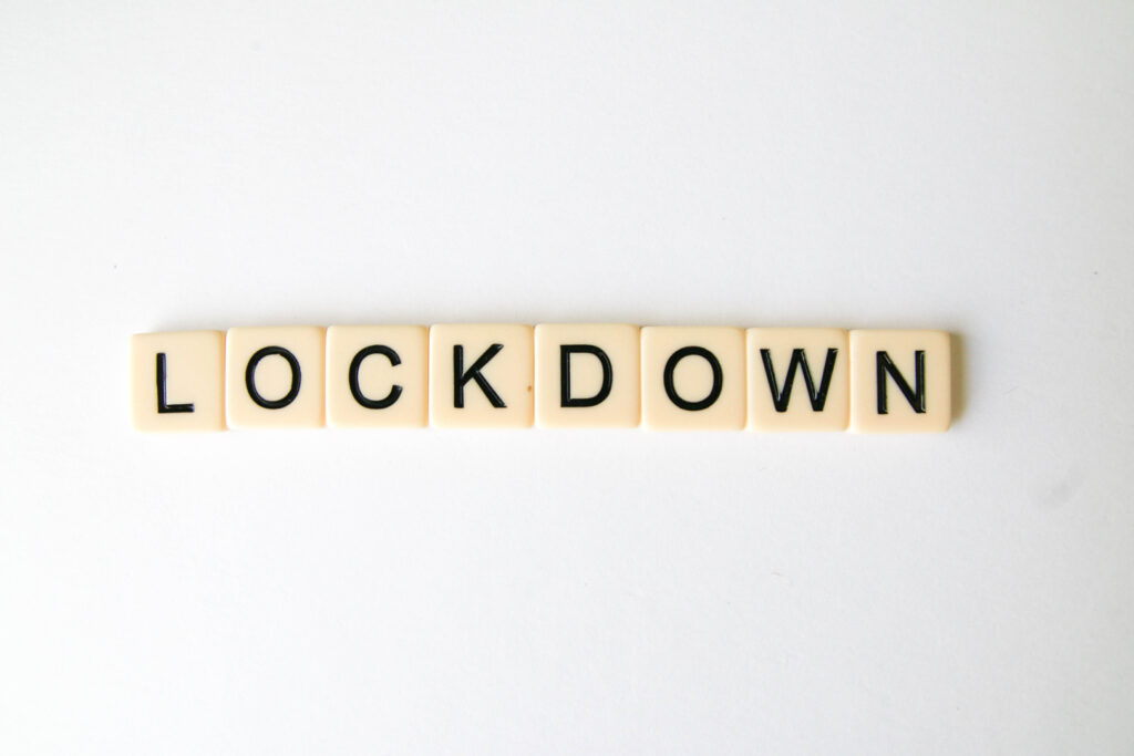 Scrabble letter pieces spelling 'lockdown'.