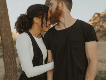 Red-bearded man kisses curly-haired woman on the forehead with a barren landscape in the background.
